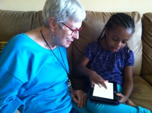 My granddaughter, Aster, showing me how she uses the Kindle, summer 2013.